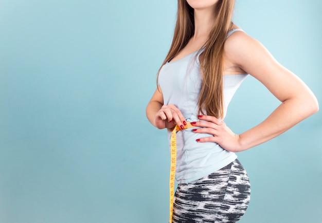 Mujer que mide la cintura con cinta Foto gratis