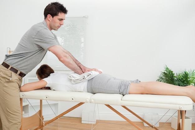 Mujer que miente mientras que es masajeada con una toalla Foto Premium