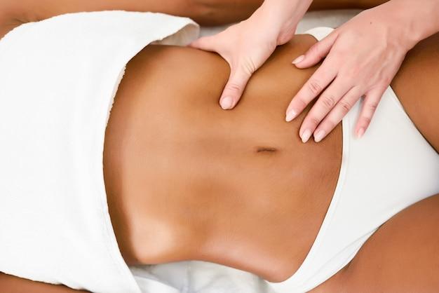 Mujer que recibe el masaje del abdomen en el centro de spa spa. Foto gratis