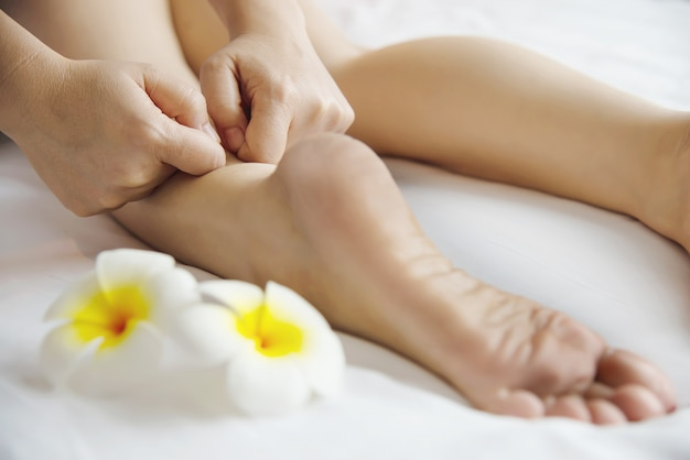 Mujer que recibe servicio de masaje de pies desde masajista de cerca a mano y pie - relájese en el concepto de servicio de terapia de masaje de pies Foto gratis