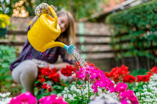 Mujer que riega las plantas de jardín de flores. mujer que cuida sus  plantas (y las riega) en su jardín. | Foto Premium