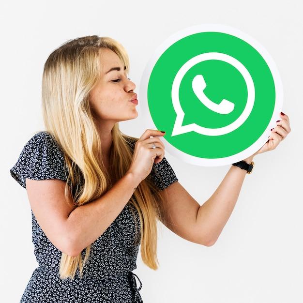 Mujer que sopla un beso a un ícono de whatsapp messenger Foto gratis
