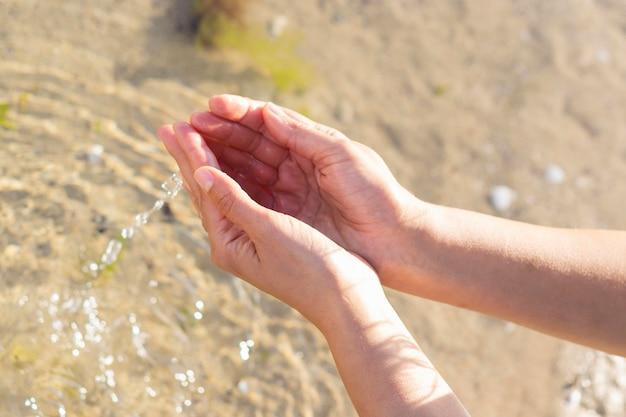 Mujer que sostiene el agua clara en sus manos Foto gratis