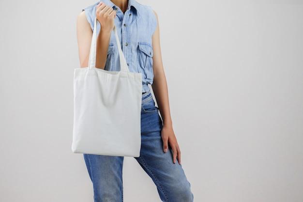 Mujer que sostiene el aislante del bolso de la tela del eco en fondo gris Foto Premium