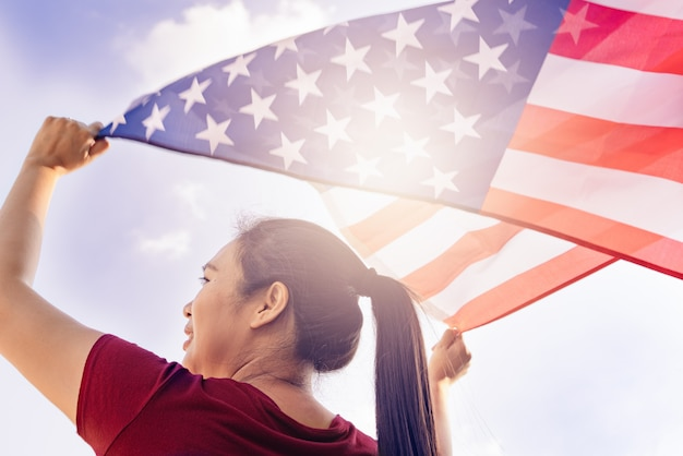 Mujer que sostiene la bandera de los estados unidos de américa en el cielo soleado. día de los caídos en los estados unidos y el concepto del día de la independencia. Foto Premium
