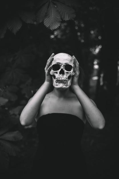 Mujer que sostiene el cráneo humano en el bosque Foto gratis