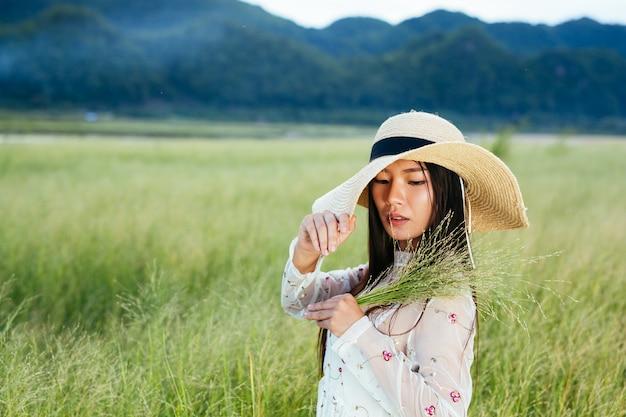 Una mujer que sostiene una hierba en sus manos en un hermoso campo de hierba con una montaña. Foto gratis