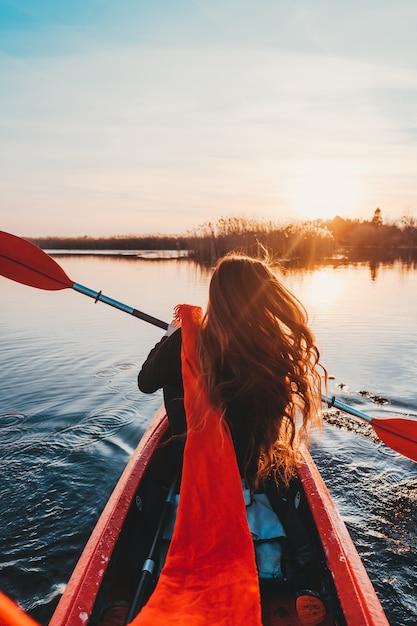 Mujer que sostiene la paleta en un kayak en el río Foto gratis