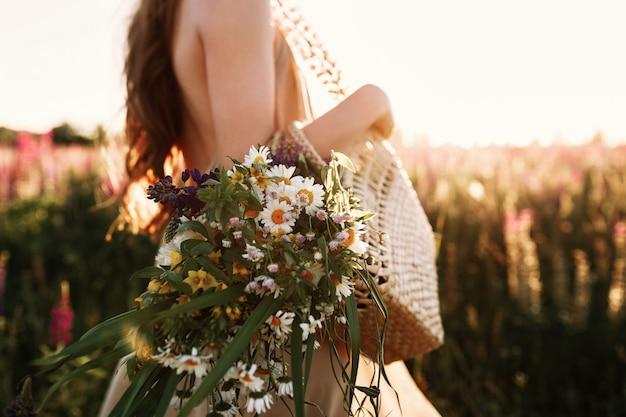 Mujer que sostiene el ramo de los wildflowers en el bolso de la paja, caminando en campo de flor en puesta del sol. Foto gratis