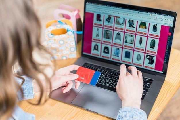 Mujer que sostiene la tarjeta de crédito frente a la computadora portátil con el sitio web de compras Foto Premium