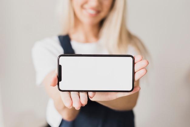 Mujer que sostiene el teléfono inteligente con maqueta Foto gratis