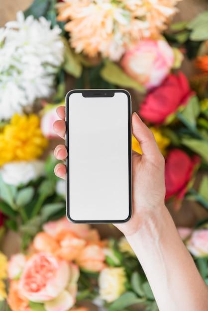 Mujer que sostiene teléfono inteligente con pantalla en blanco por encima de las flores Foto gratis