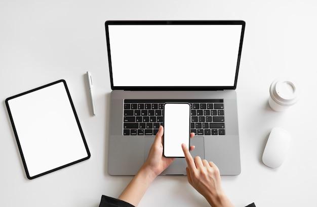 La mujer que sostiene el teléfono, el ordenador portátil y la tableta elegantes en la tabla, imitan para arriba de la pantalla en blanco. Foto Premium
