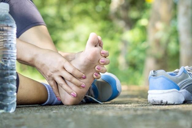 Mujer que sufre de dolor en el pie durante el deporte. Foto Premium