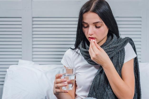 Mujer que sufre de frío sosteniendo vaso de agua tomando medicina Foto gratis