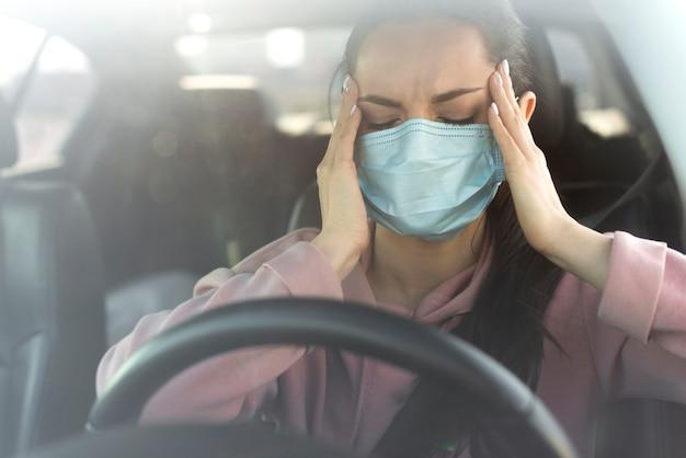 Mujer que tiene un dolor de cabeza en el auto Foto Premium