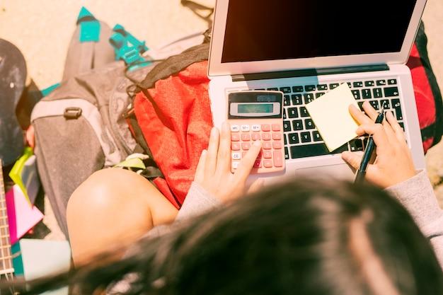 Mujer que toma notas a mano con la calculadora en la computadora portátil en día soleado Foto gratis