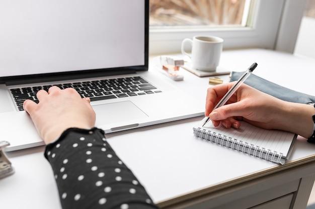 Mujer que trabaja en la computadora portátil y notas de tareas Foto gratis