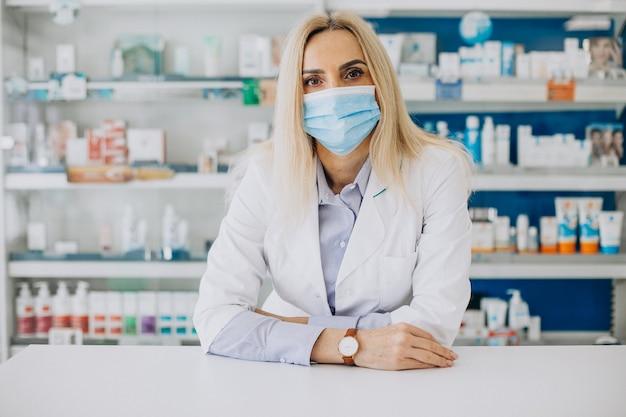 Mujer que trabaja en la farmacia y vistiendo abrigo Foto gratis