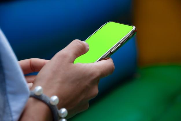 Mujer que usa la aplicación móvil en el teléfono inteligente con una pantalla verde de chromakey Foto Premium