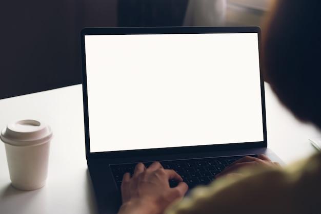 Mujer que usa la computadora portátil en la mesa, se burlan de la pantalla en blanco. Foto Premium