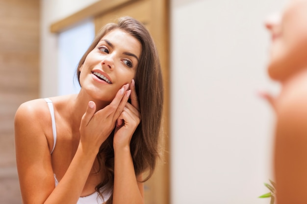 Mujer quitando la espinilla de su rostro Foto gratis