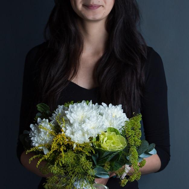 Una mujer con un ramo de flores blancas como la nieve en la mano en el espacio de tiro Foto gratis