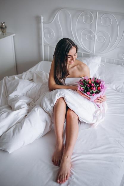 Mujer con ramo de flores en la cama Foto gratis