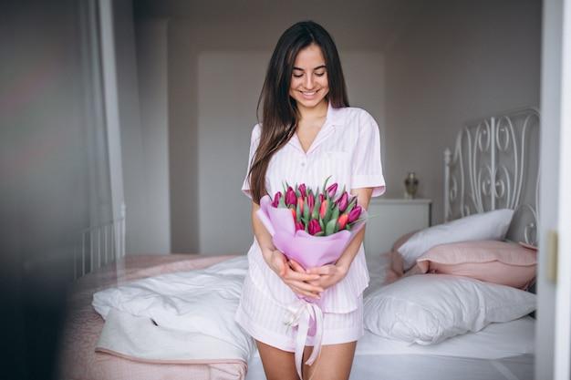Mujer con ramo de flores en dormitorio Foto gratis