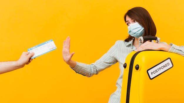 Mujer rechazando un boleto de avión mientras usa una máscara médica e Foto gratis