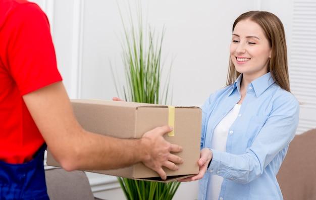 Mujer recibe una caja de cartón de mensajería Foto gratis