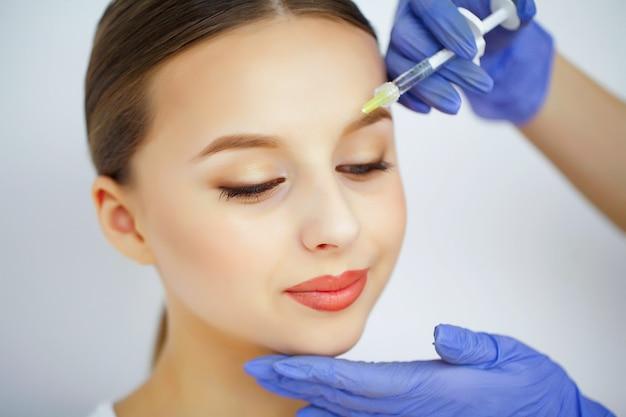 La mujer recibe una inyección en la cara. Foto Premium