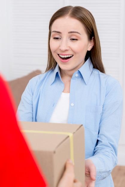 Mujer recibiendo una caja de cartón y ser feliz Foto gratis