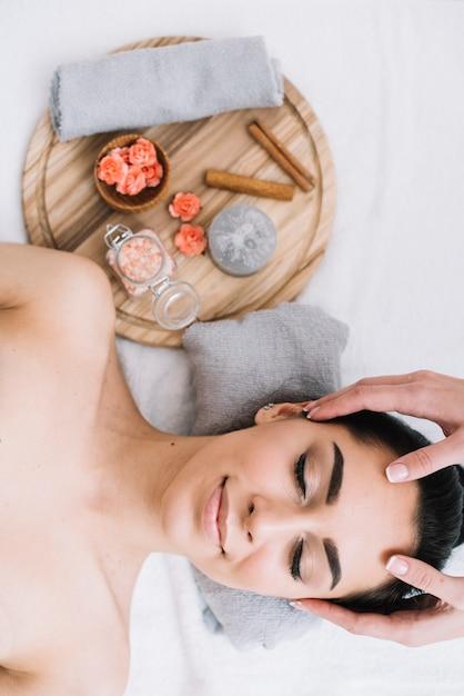 Mujer recibiendo un masaje facial relajante Foto gratis