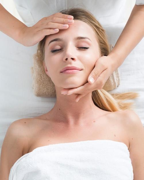 Mujer recibiendo un masaje facial en un spa Foto gratis