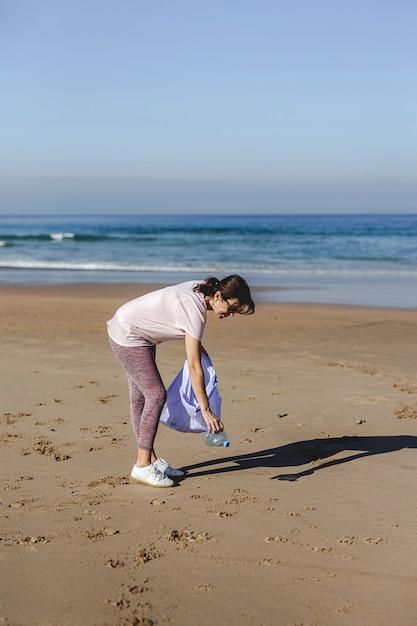 Mujer recogiendo basura y plásticos limpiando la playa Foto Premium