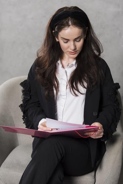 Mujer de recursos humanos sosteniendo y leyendo el currículum Foto gratis