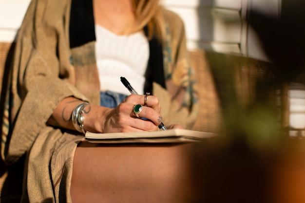 Mujer relajada escribiendo en su diario Foto gratis