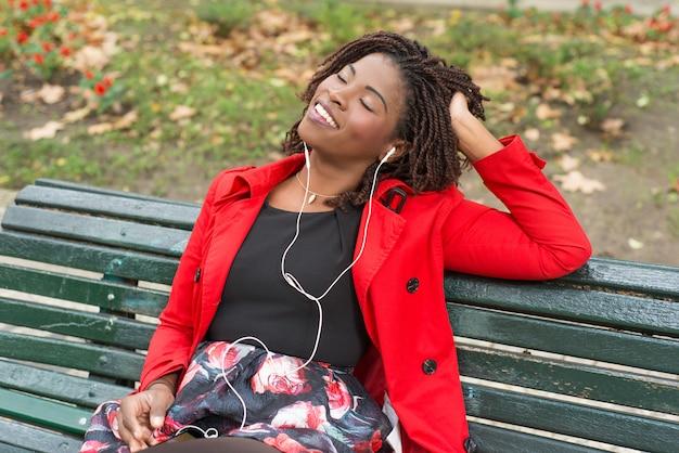Mujer relajada escuchando música en el parque Foto gratis