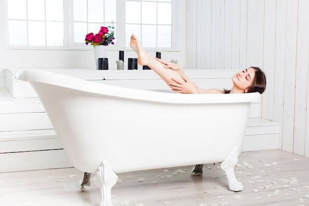Mujer relajante en la bañera en el baño elegante Foto gratis