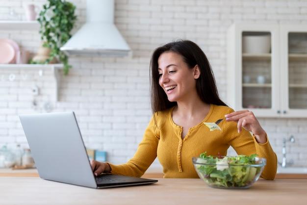 Mujer revisando laptop y comiendo ensalada Foto gratis