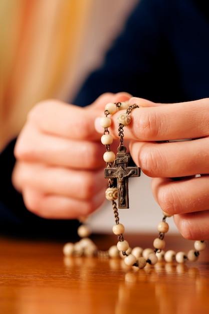 Foto Premium | Mujer rezando con rosario a dios