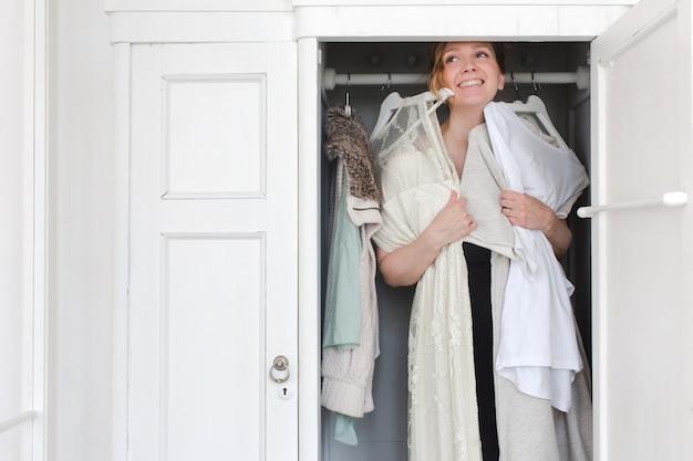 descuento más bajo obtener nueva Reino Unido La mujer se ríe mientras elige ropa en el armario ...