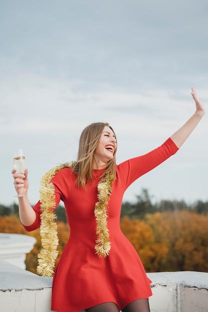 Mujer riendo en vestido rojo divirtiéndose en la azotea Foto gratis