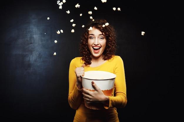 Mujer riendo vomitando palomitas de maíz en el aire Foto gratis