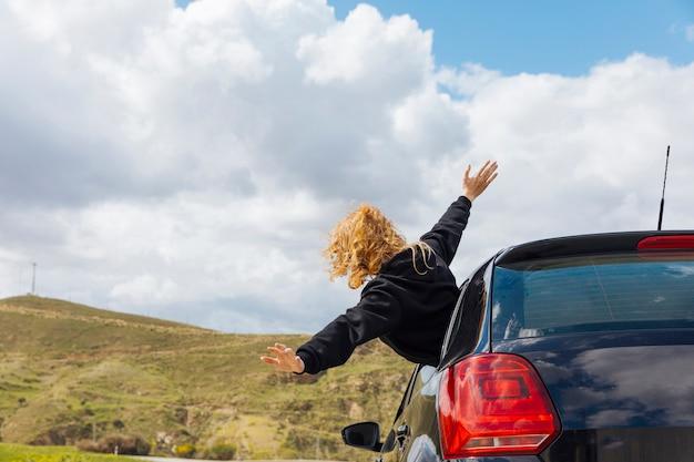 Mujer rizada joven que se inclina fuera de la ventana de coche Foto gratis
