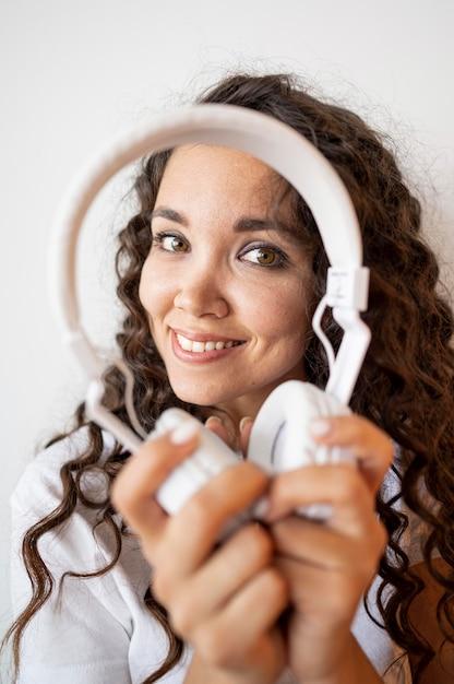 Mujer rizada sonriente que sostiene un par de auriculares Foto gratis