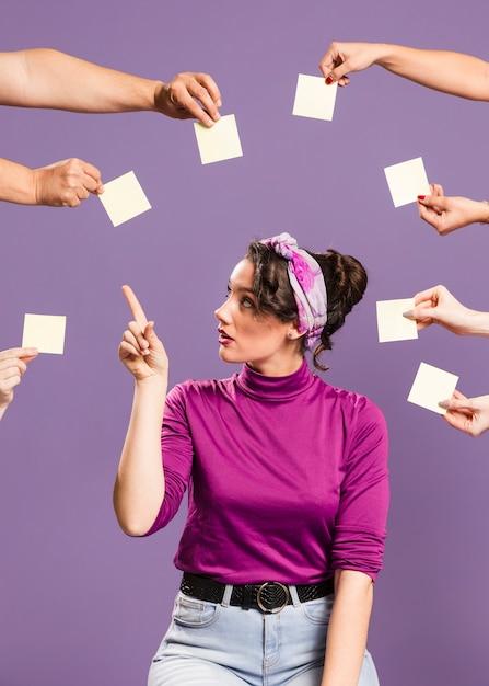 Mujer rodeada de manos y notas adhesivas escogiendo una nota vacía Foto gratis