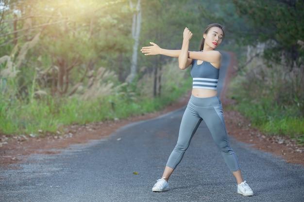 Mujer en ropa deportiva haciendo ejercicios al aire libre Foto gratis
