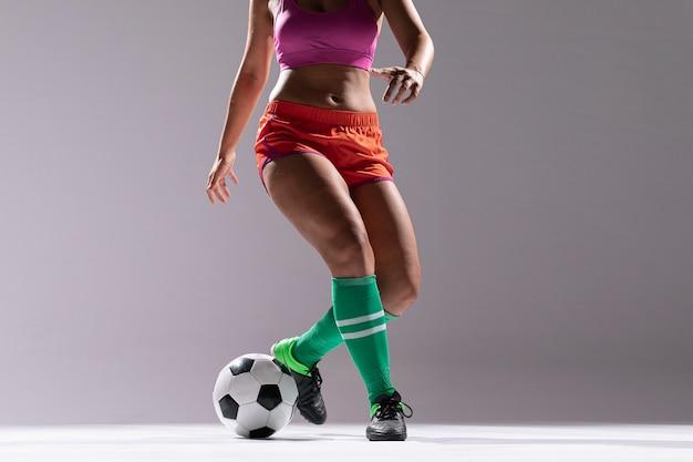 Mujer en ropa deportiva jugando al fútbol Foto gratis